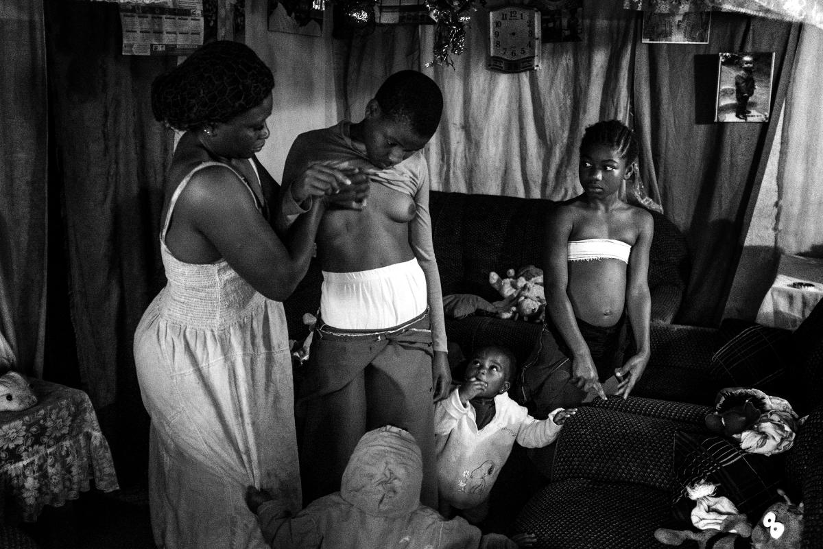 Гэба Хаміс, Егіпет. 28-гадовая Вэроніка масажуе грудзі сваёй 10-гадовай дачцэ Мішэль пад позіркамі іншых дзяцей.
