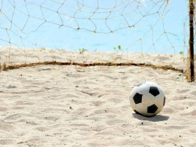 76438475 football on a beach soccer leather ball on beach with sea in the background